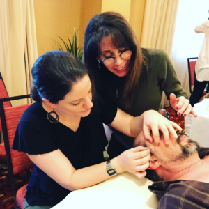CEU student practicing cosmetic acupuncture while Michelle Gellis looks on